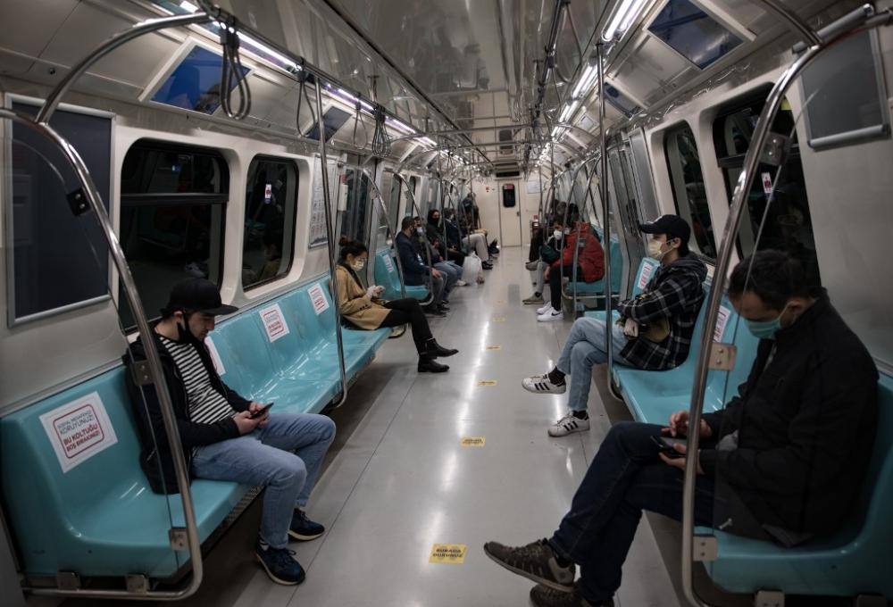 People wearing a face mask sit on the metro while respecting social distancing in Istanbul, Turkey, on 7 May 2020. By Cem Tekkeşinoğlu / AFP.