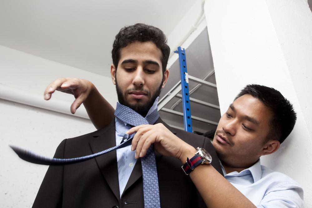 "Patrick Zachmann pictured this scene above at ""La Cravate Solidaire,"" an association that trains jobseekers before recruiting interviews. Here an advisor teaches how to tie a tie"