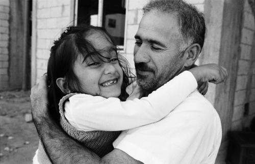 On this picture by Giles Duley taken in 2016. Aya, a young Syrian refugee, hugs her father as they prepare to be resettled from Lebanon to France.