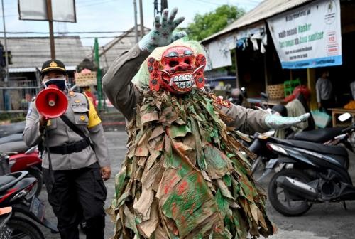 "A Bali police officer wears a scary mask called ""Leak"" while trying to educate people on COVID-19 coronavirus matter at a traditional market in Kerobokan, near Denpasar on May 14, 2020"